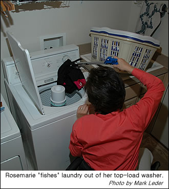 Rosemarie uses a reacher to get laundry out of an upright washer