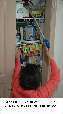 Rosemarie using a reacher inside the pantry at her existing home